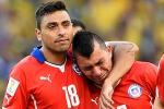 Chile's Gonzalo Jara (L) comforts his teammate Gary Medel after losing their 2014 World Cup round of 16 game against Brazil at the Mineirao stadium in Belo Horizonte