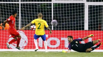 Jun 12, 2016; Foxborough, MA, USA; Peru forward Raul Ruidiaz (11) scores on Brazil goalkeeper Alisson Becker (1) as Brazil defender Daniel Alves (2) looks on during the second half of Peru's 1-0 win over Brazil in the group play stage of the 2016 Copa America Centenario. at Gillette Stadium. Mandatory Credit: Winslow Townson-USA TODAY Sports