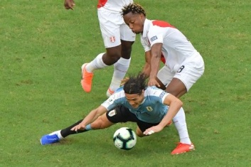 Uruguay's Edinson Cavani falls next to Peru's Andre Carrillo during their Copa America football tournament quarter-final match at the Fonte Nova Arena in Salvador, Brazil, on June 29, 2019. (Photo by Luis ACOSTA / AFP)