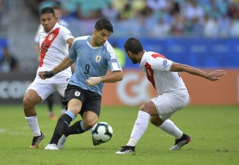 Uruguay's Luis Suarez (C) is marked by Peru's Luis Abram (R) and Peru's Edison Flores during their Copa America football tournament quarter-final match at the Fonte Nova Arena in Salvador, Brazil, on June 29, 2019. (Photo by Raul ARBOLEDA / AFP)